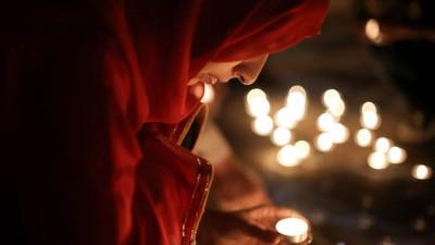 Woman at candlelight vigil.