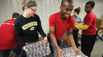 Students stack cans.