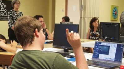 Young man raising hand in classroom.