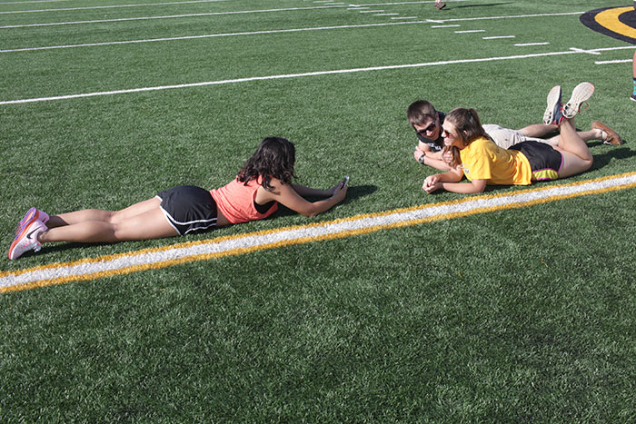 Students taking cell phone photos on the field.