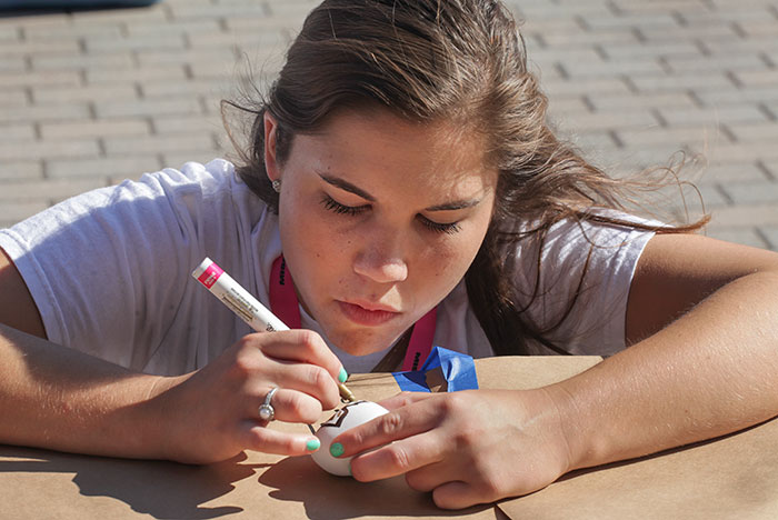 Student drawing on a rock.