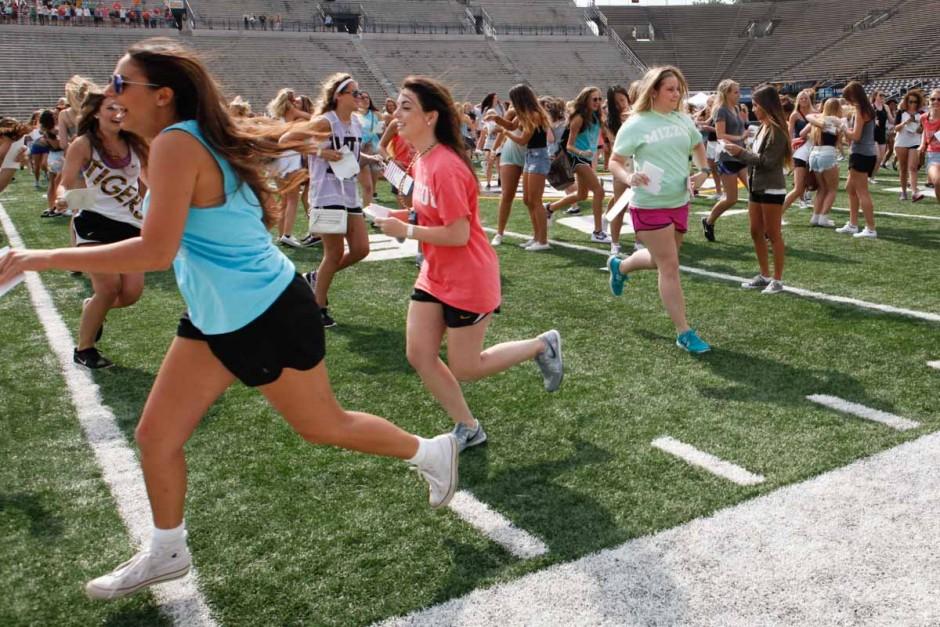 Girls running on the football field.