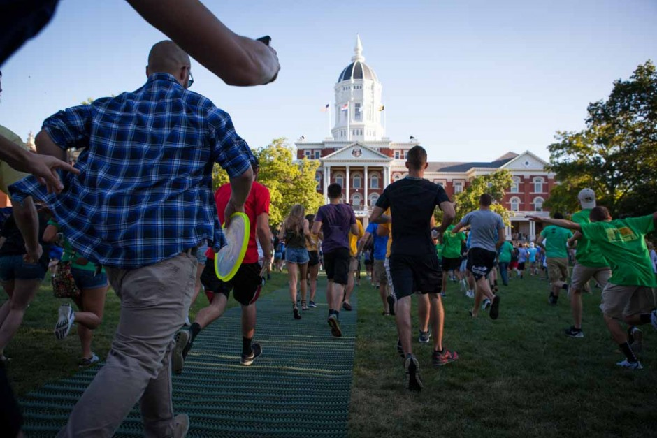 After students passed through the columns on the Quad, it became a race to Jesse Hall in a fit of excitement. Many of the freshmen stopped to high-five Chancellor Loftin and stop for a selfie. Photo by Tanzi Propst.