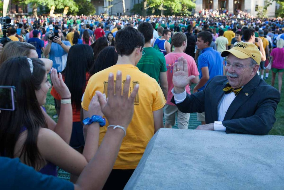 Students stop to high-five Chancellor Loftin as they pass through the columns on their way to Jesse Hall Sunday evening. The Chancellor stayed behind the base of the columns so as to not be runover by the stempede of students that raced toward Jesse Hall. Photo by Tanzi Propst.