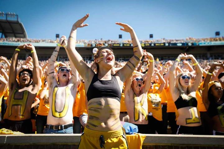 Students in body paint cheering in Memorial Stadium.