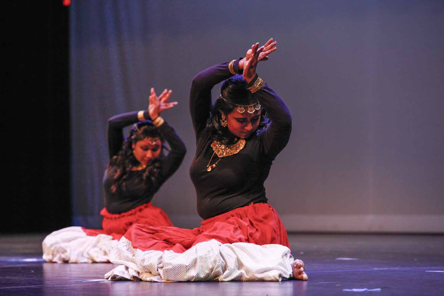 Dancers posing in seated position on stage.