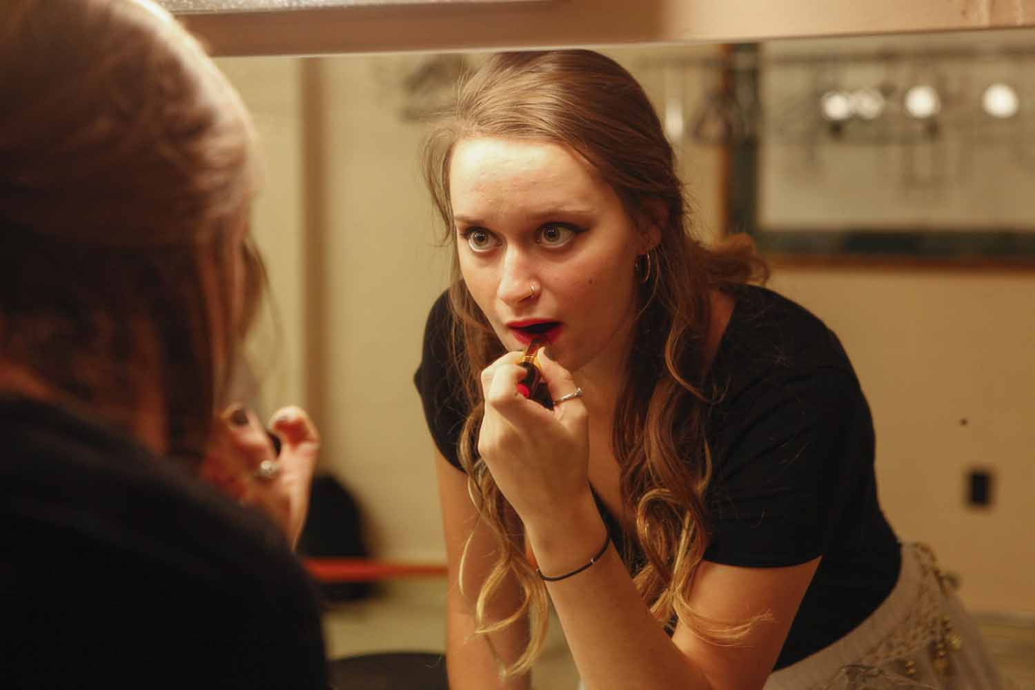 Paige Kiehl puts on lipstick in the mirror as she gets ready to perform with her group, Mizzou Masti, as part of India Nite at Jesse Hall.
