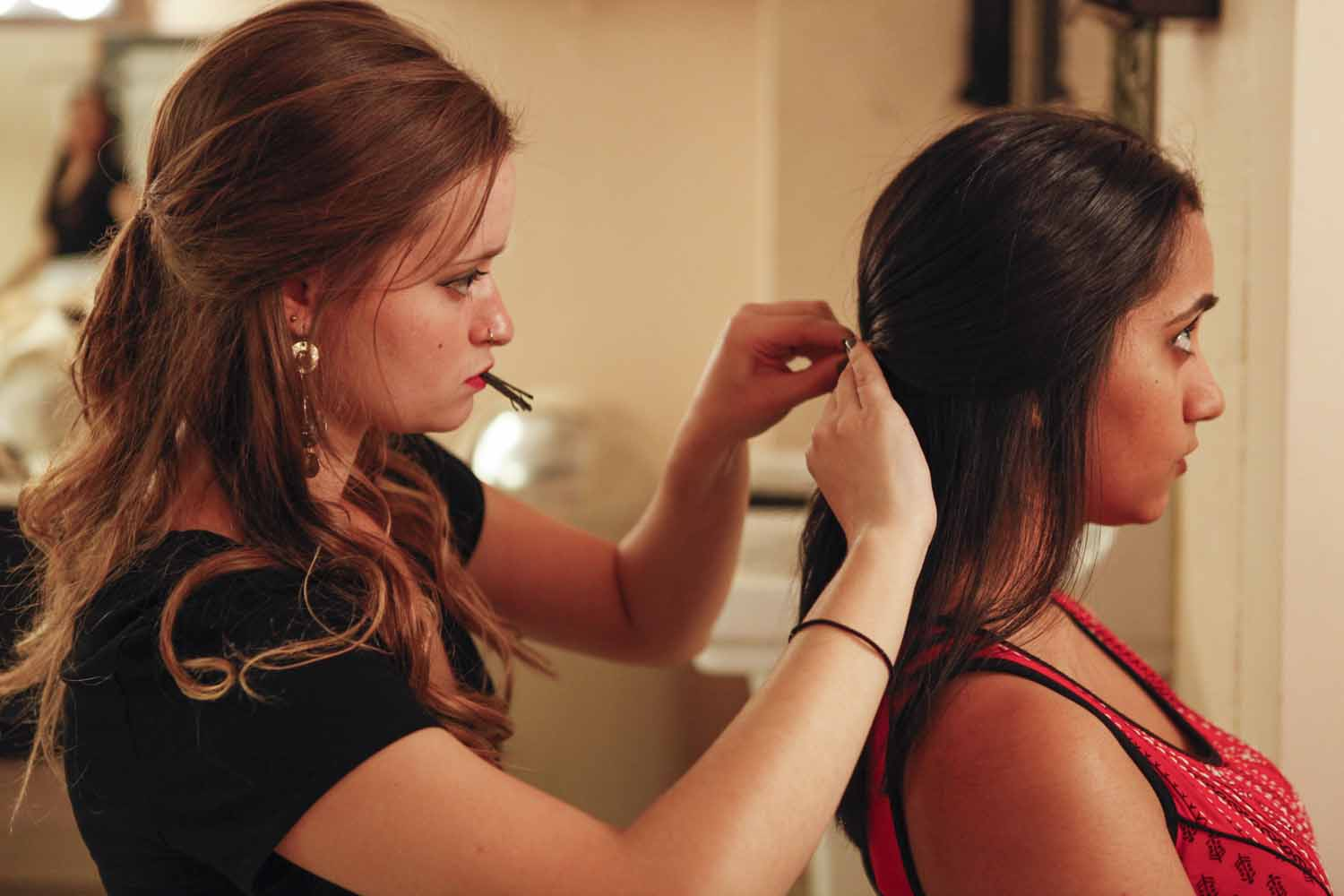 Paige Kiehl helps fellow Mizzou Masti member Sumidha Katti pin her hair back in the dressing room before their performance during the second act of India Nite at Jesse Hall.