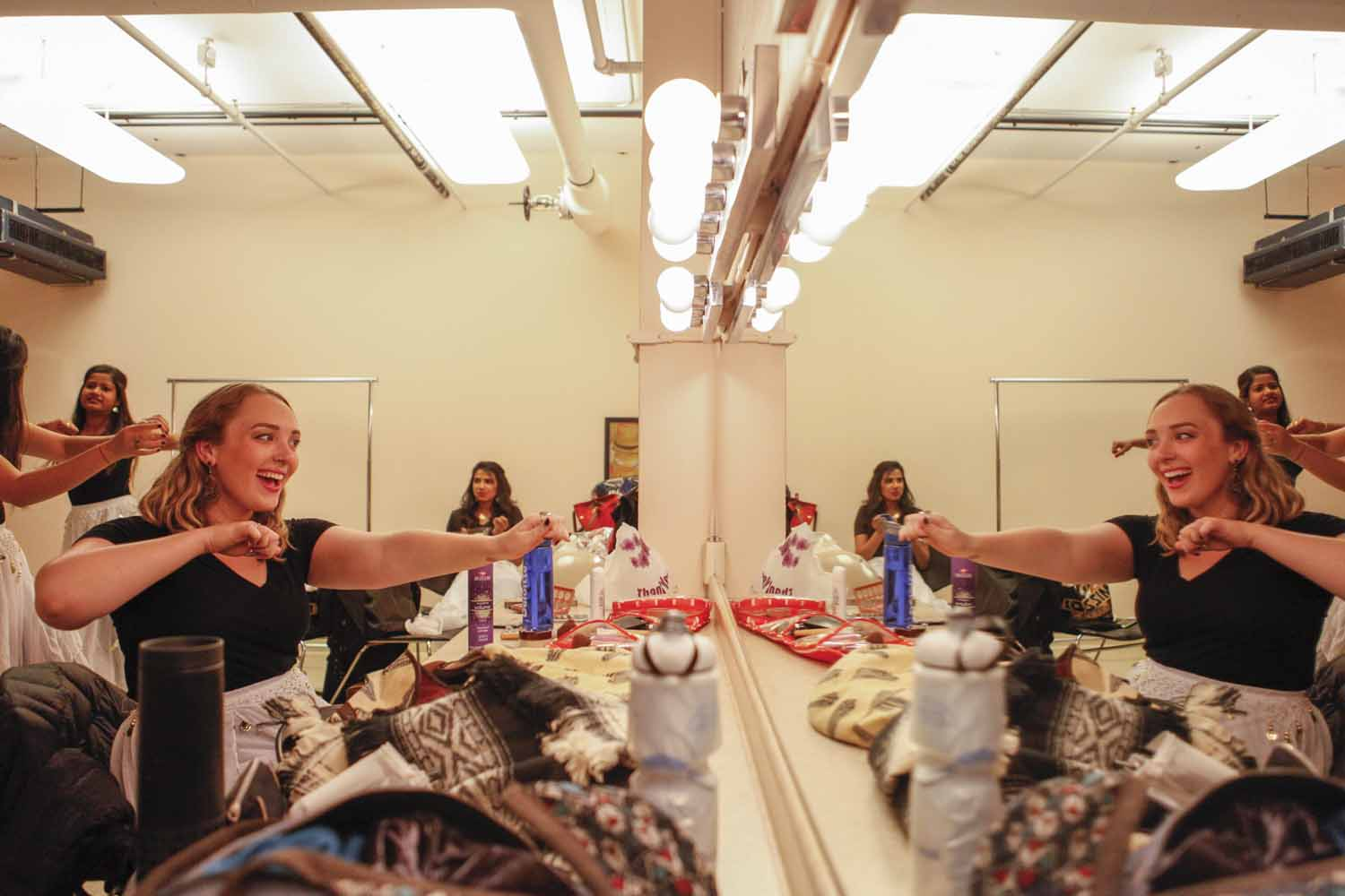 Kelsey Burns practices arm movements to her group's upcoming performance in the mirror of a dressing room in Jesse Hall as the rest of the ensembe dances around the room.