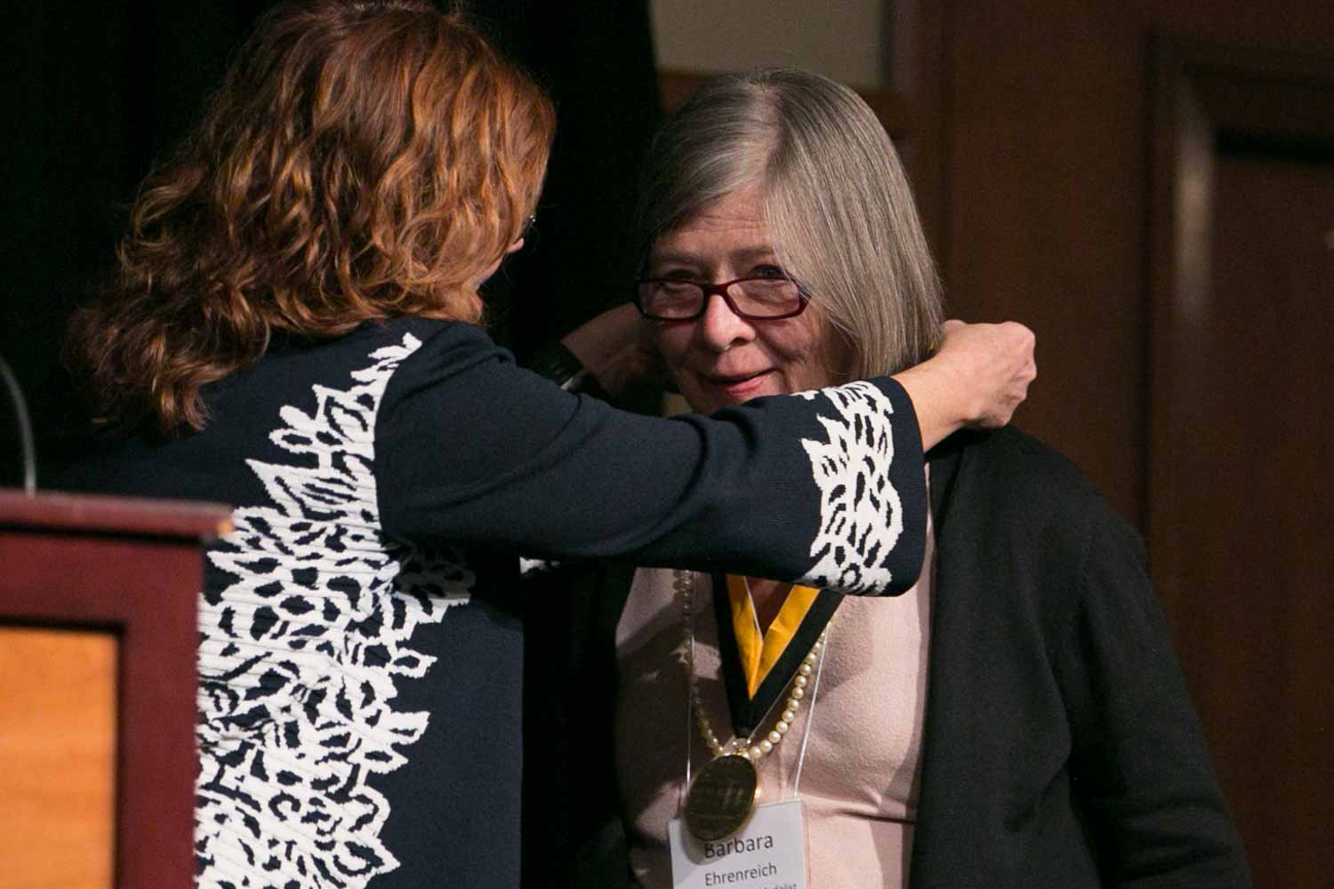 """Author and activist Barbara Ehrenreich receives her honor medal. Ehrenreich is the author of 21 books, including The New York Times best sellers, """"Nickel and Dimed: On (Not) Getting By in America"""" (2001), """"Bright-Sided: How Positive Thinking Is Undermining America"""" (2010), and """"Living with a Wild God"""" (2014). Ehrenreich is also a frequent contributor to The New York Times, Harpers, The Progressive magazine, and Time magazine, and has appeared on """"Oprah, The Daily Show."""""""