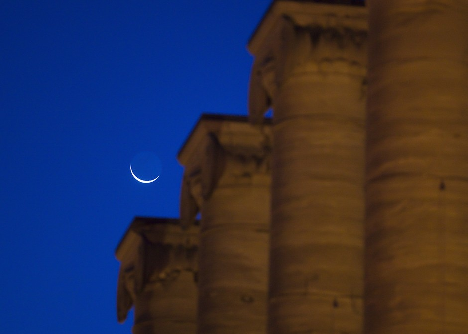 A crescent moon sets over the columns