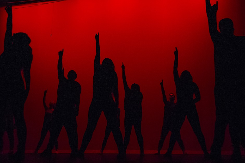 Silhouetted dancers pointing upward