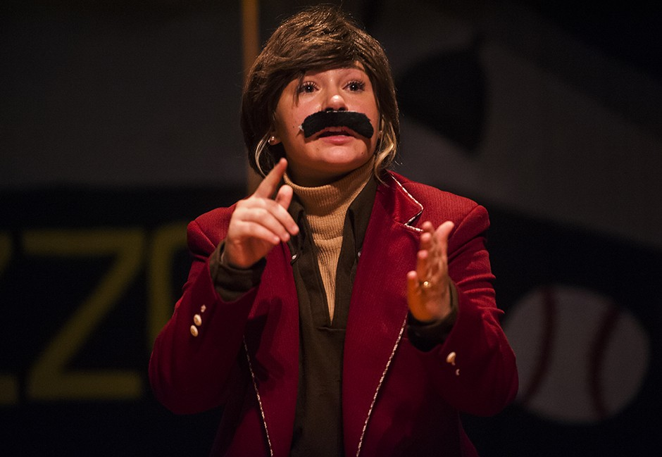 A performer dressed as Ron Burgundy acts out a skit