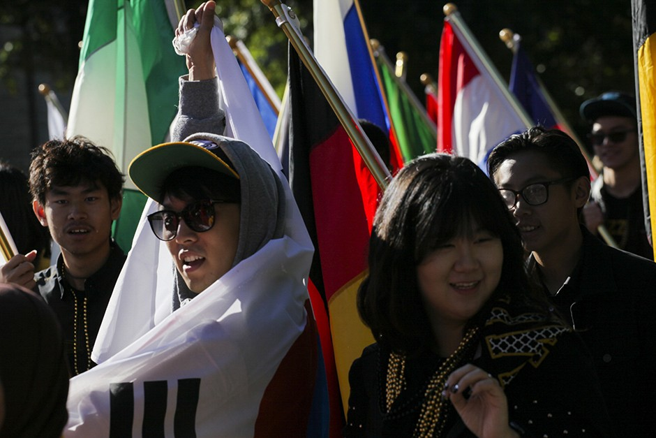 Students support the MU International Center by carrying the flags of the countries represented by students at Mizzou. Photo by Nicholas Benner