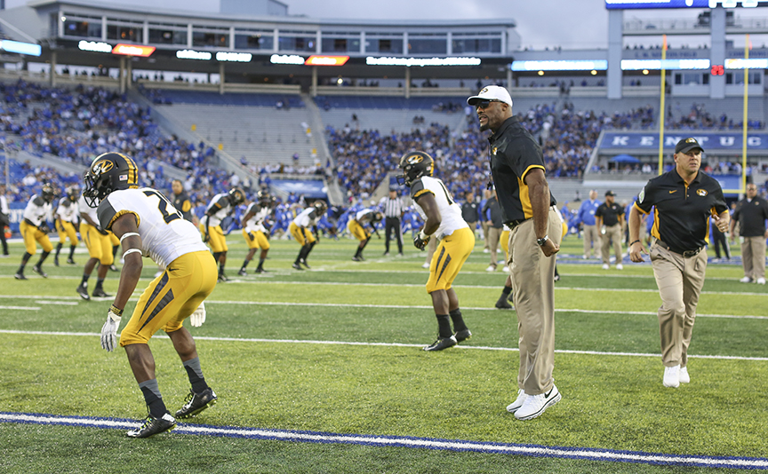 Coach and players warm up on football field.