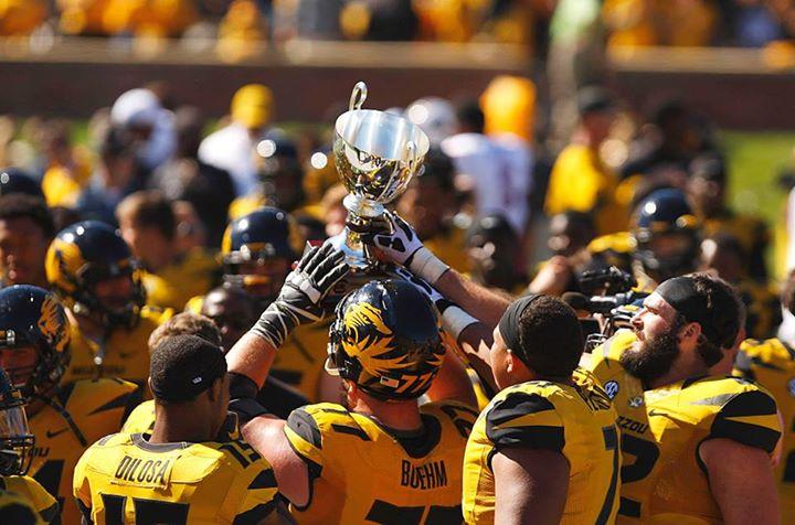 Football players raising a trophy.