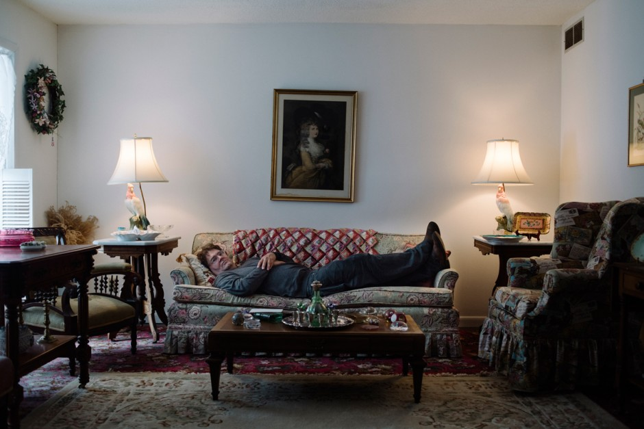 George Hodgman on a couch in his mother's living room.