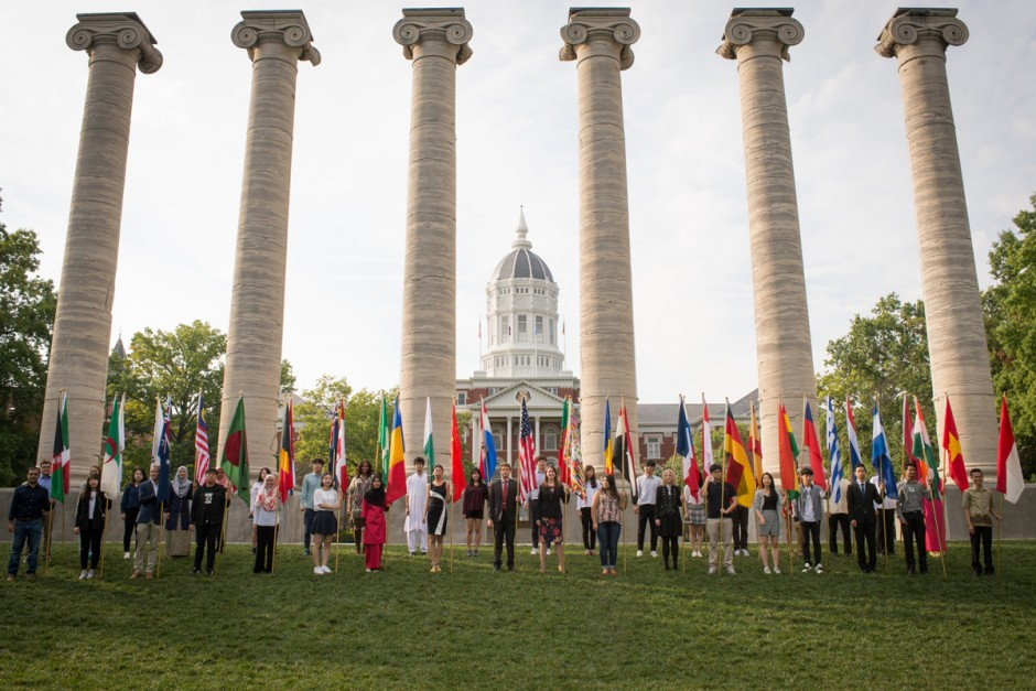 Students hold international flags in front of the Columns.