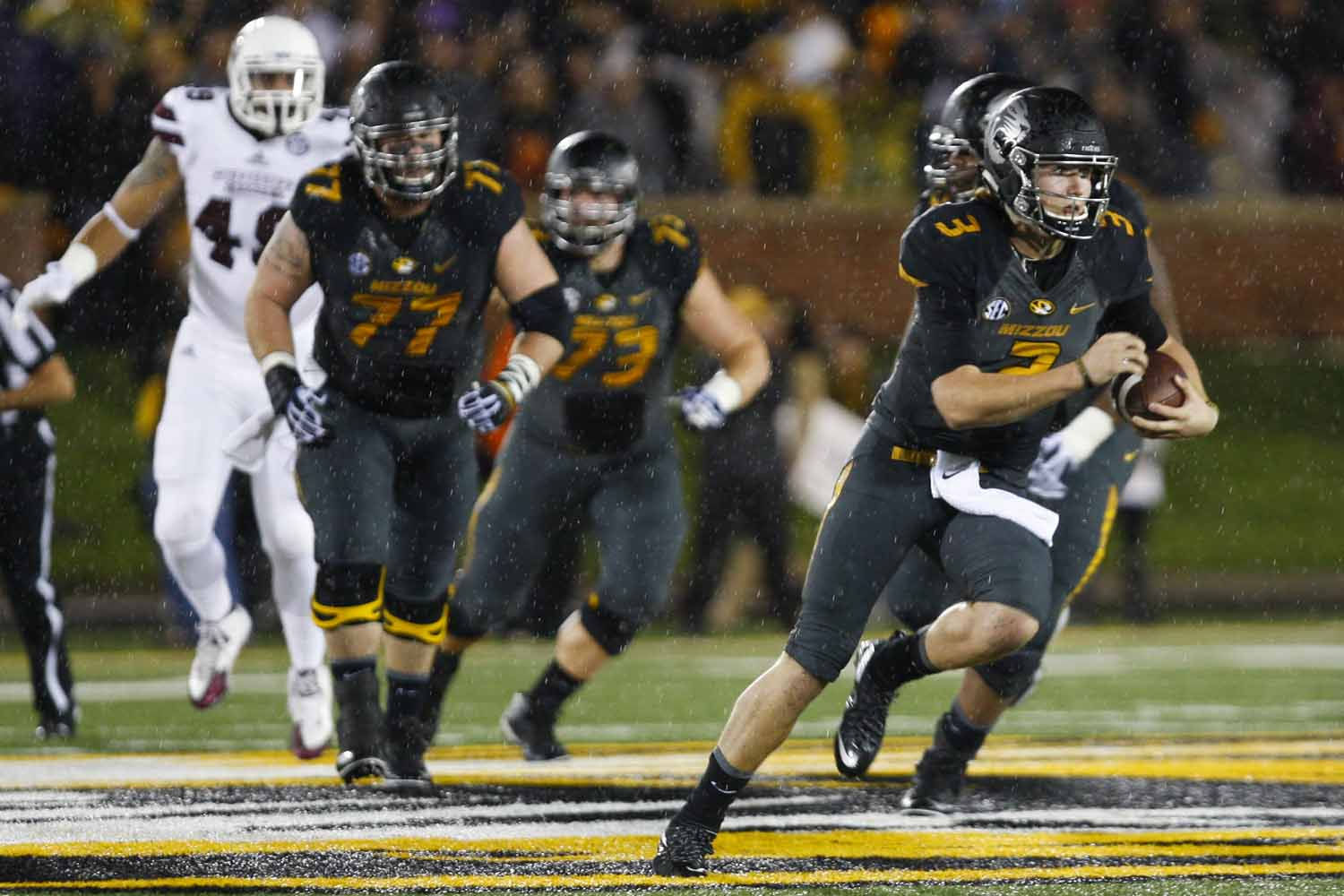 Drew Lock, right, advances the ball, running downfield during the first half of the game against Mississippi State, Thursday evening. Photo by Tanzi Propst.