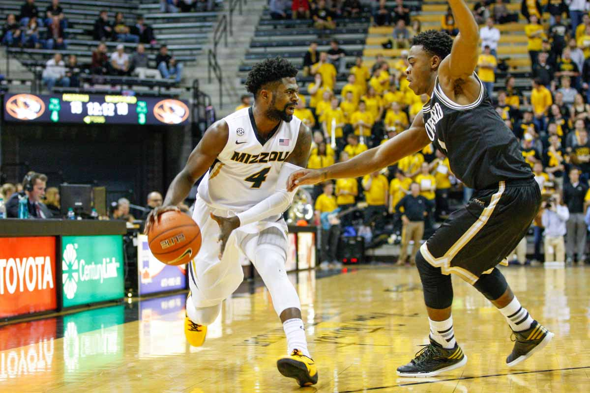 Tramaine Isabell (4), a guard for the Tigers, dribbles the ball and yells to his teammates as Wofford's Derrick Brooks, right, tries to block Isabell's next move, Friday at Mizzou Arena.