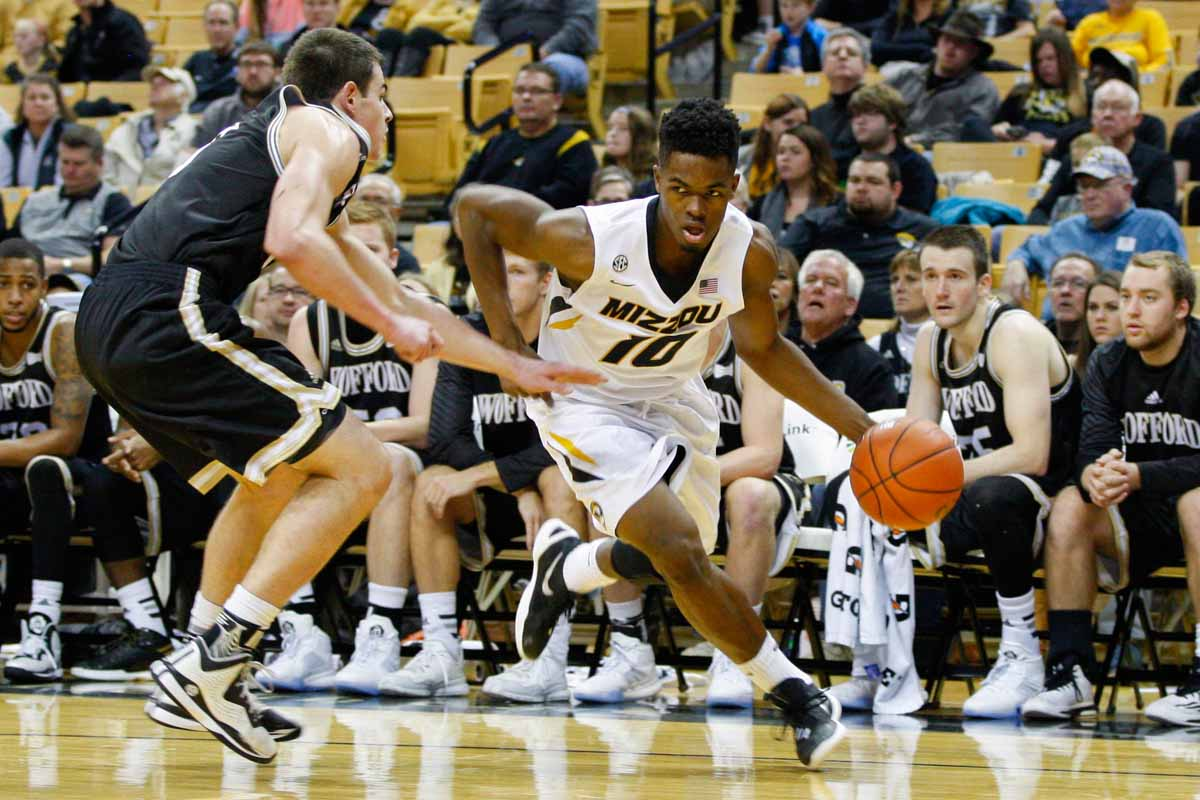 K.J. Walton (10) dribbles towards the basket, trying to evade Fletcher Magee, left, a guard for the Terriers, Friday at Mizzou Arena.