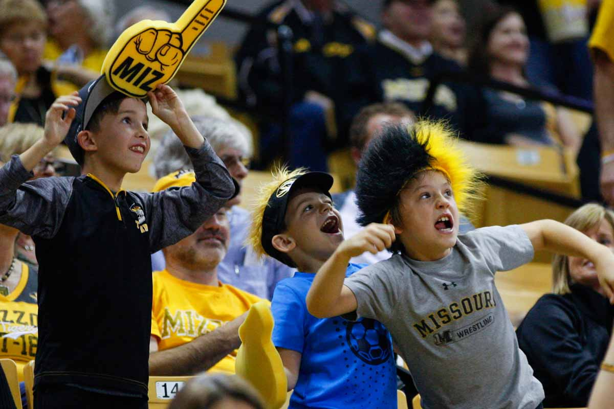 From left, Dylan Hamm, 9, Graden Anderson, 6, and Frank Hazelrigg, 9, get their game-faces on as they show off and cheer for the video board during halftime of the game against the Wofford Terriers Friday at Mizzou Arena. The three are on the Columbia Wrestling Club together.