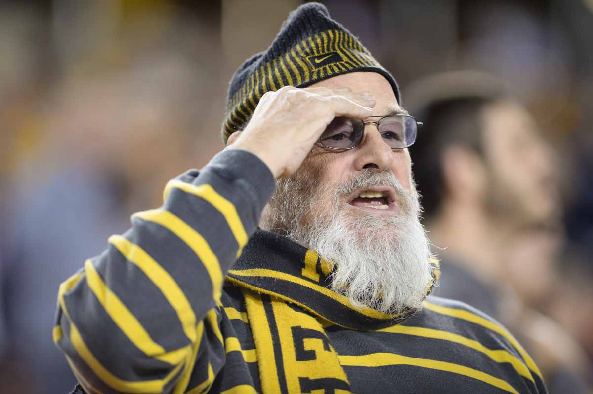A patriotic black and gold fan salutes the red, white and blue during the National Anthem. Photo by Shane Epping.