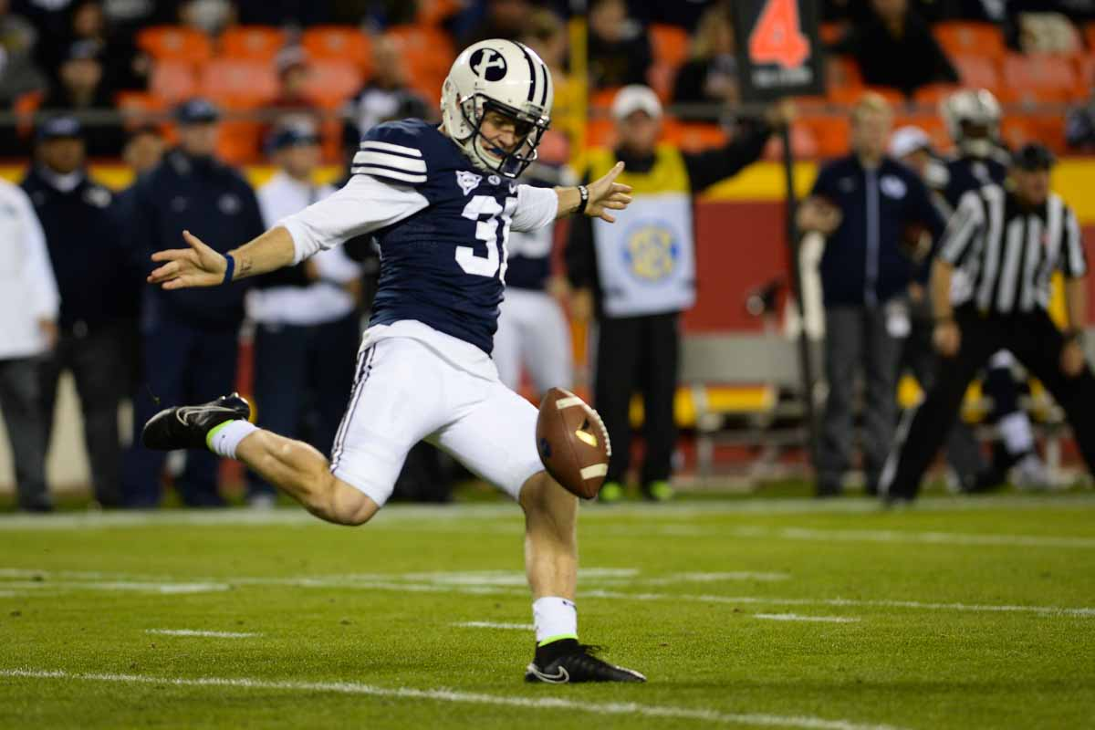 Junior punter Jonny Linehan kicks the ball after BYU fails to convert on a third down. Photo by Shane Epping.