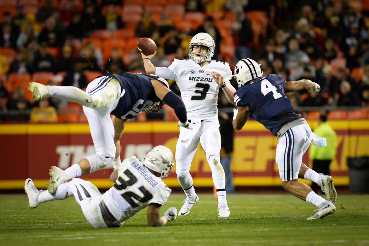 Freshman quarterback Drew Lock completes a pass before BYU's defense can tackle him. Photo by Shane Epping.
