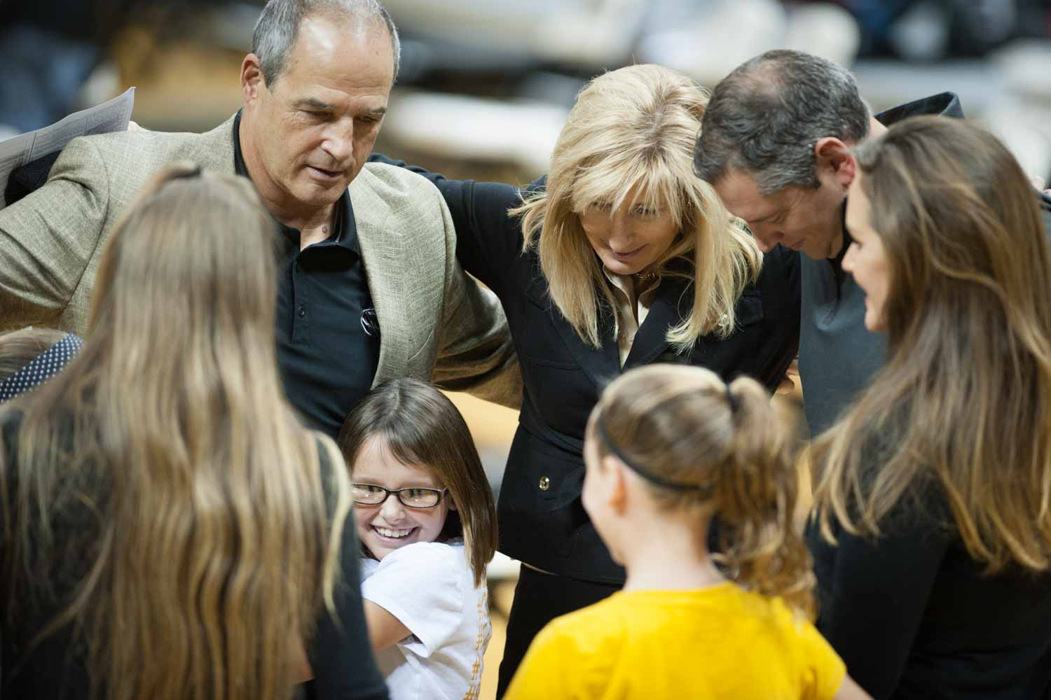 Members of coach Pinkel's family form a circle and embrace one another before leaving the press conference.