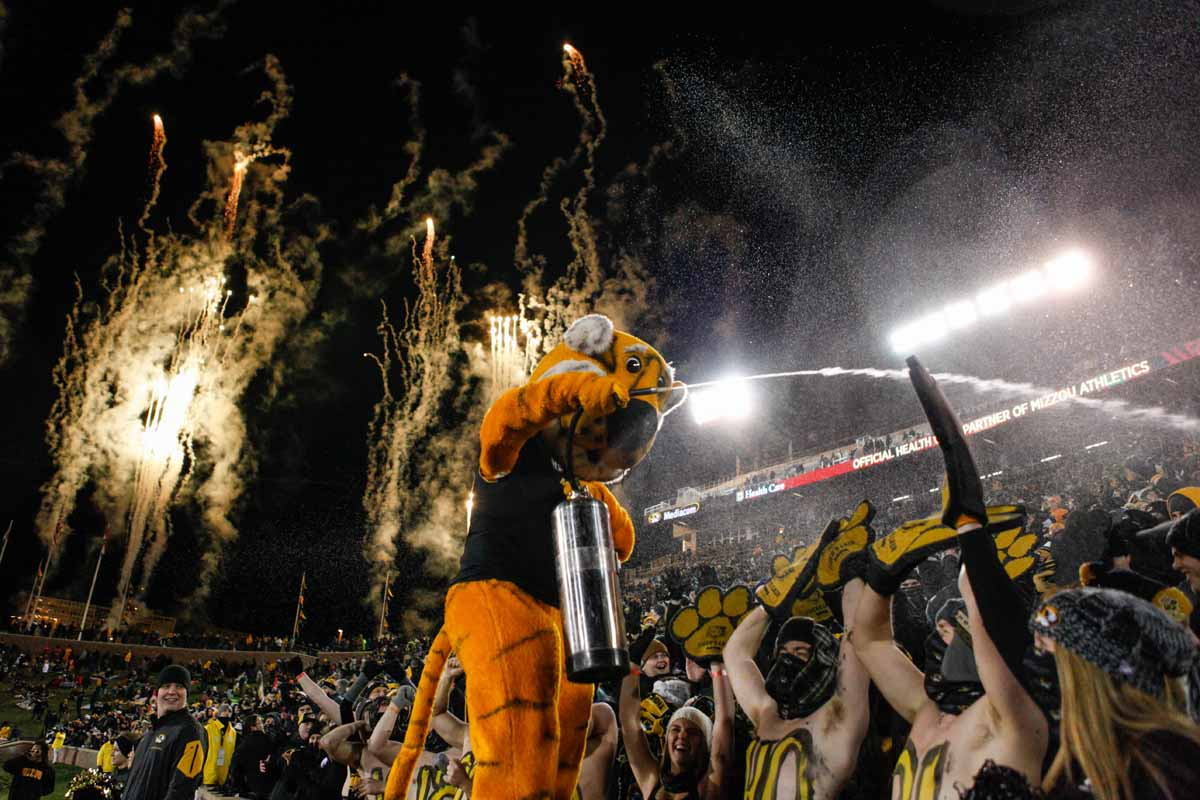 Truman the Tiger gives the front section of Tiger's Lair a pre-game shower in the 25-degree temperatures as gold fireworks shoot off from the North endzone of Faurot Field Saturday evening. Photo by Tanzi Propst.