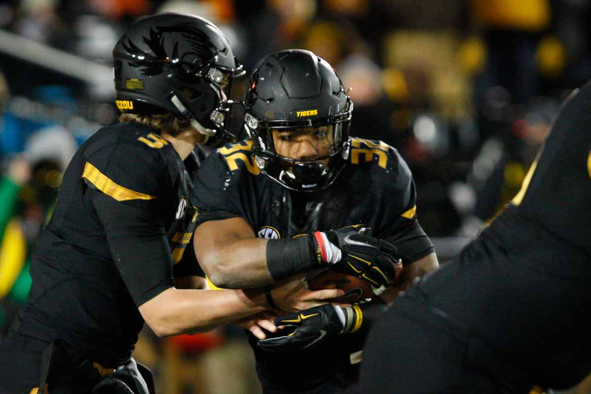 Freshman quarterback Drew Lock (3) hands the ball off to Russell Hansborough (32), a senior tailback, as the Tigers attempt to run the ball downfield in the first half of the game against the Tennessee Volunteers Saturday evening. Photo by Tanzi Propst.