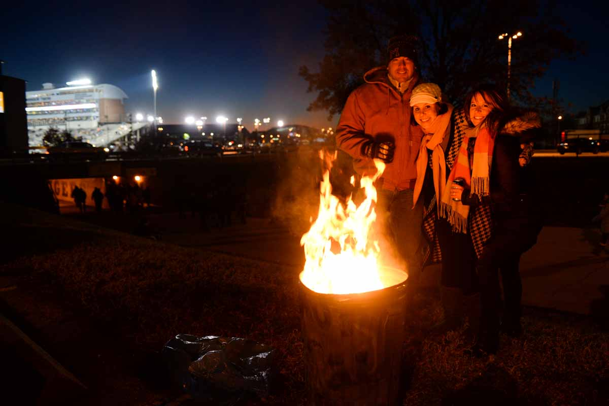 Emily Bach and a couple of her friends take advantage of a make-shift fireplace made by unknown tailgaters to stay warm before kickoff at Faurot Field. Photo by Shane Epping.