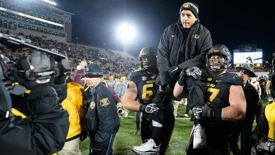 Evan Boehm, right, and Connor McGovern carry Coach Pinkel off the field. Photo by Shane Epping.
