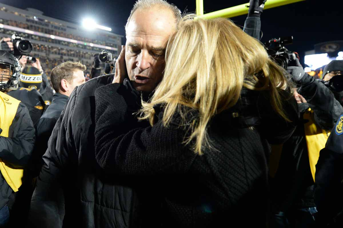 Missy Martinette Pinkel embraces her husband after players lower him to the field on his last home game. Photo by Shane Epping.