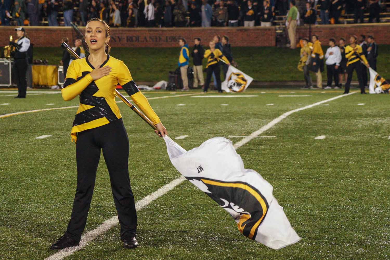 A member of the Marching Mizzou Color Guard sings the National Anthem before the game. Photo by Allison Collins.