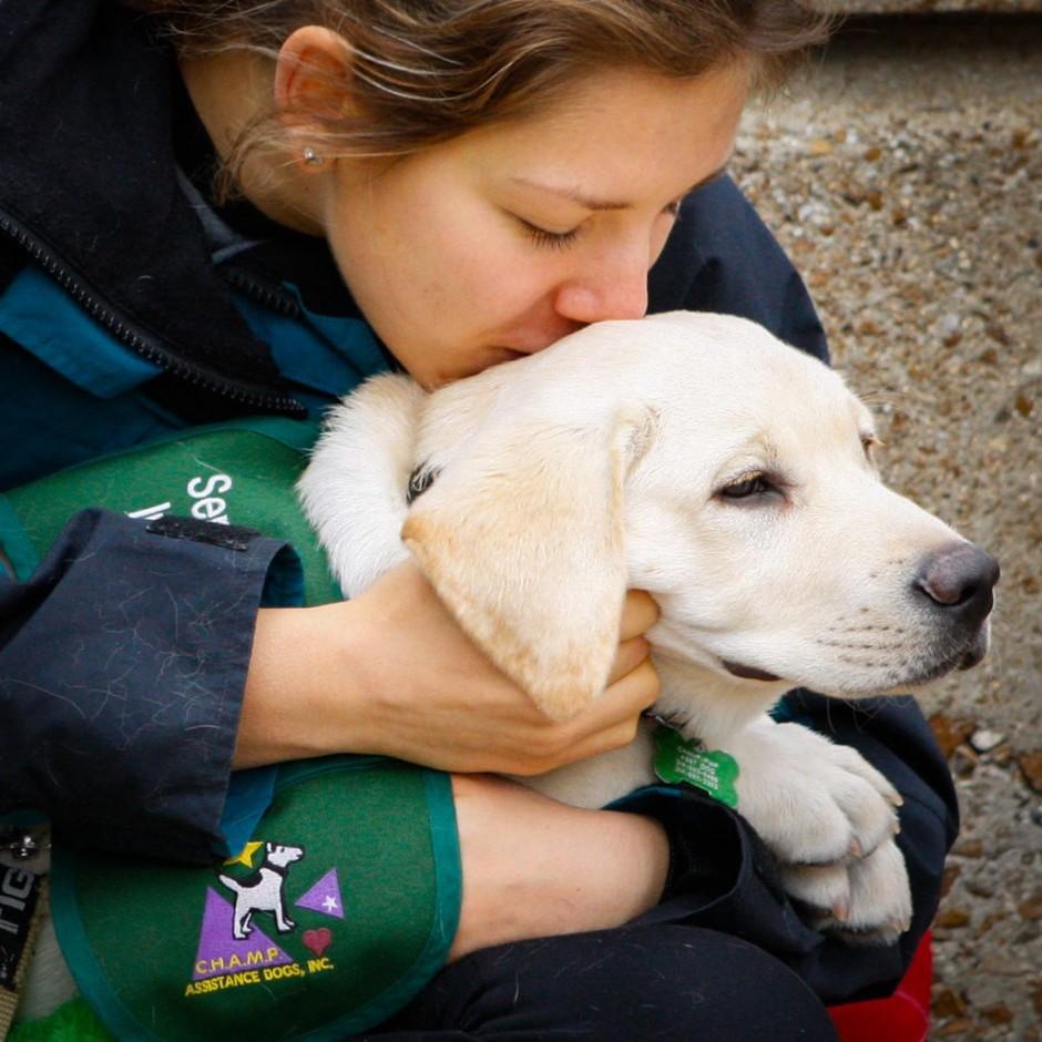 Girl holding puppy.