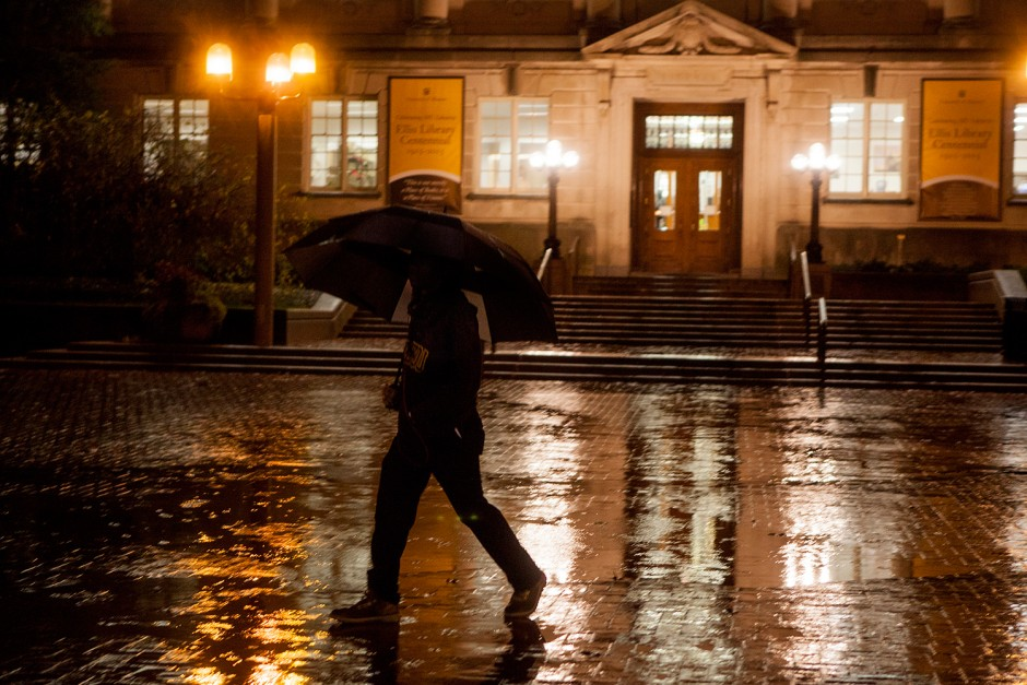 Student walking in the rain at night with an umbrella.