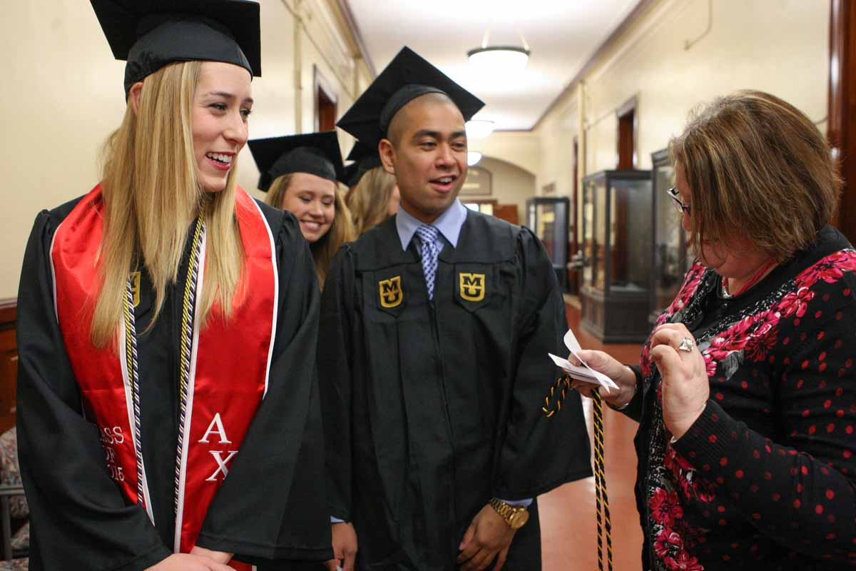 Jill Rechtien laughs with Tammy Conrad, an academic advisor for nutrition and exercise phisiology, as Conrad makes sure everyone in the NEP line is in the correct order before filing into Jesse Auditorium Friday afternoon.