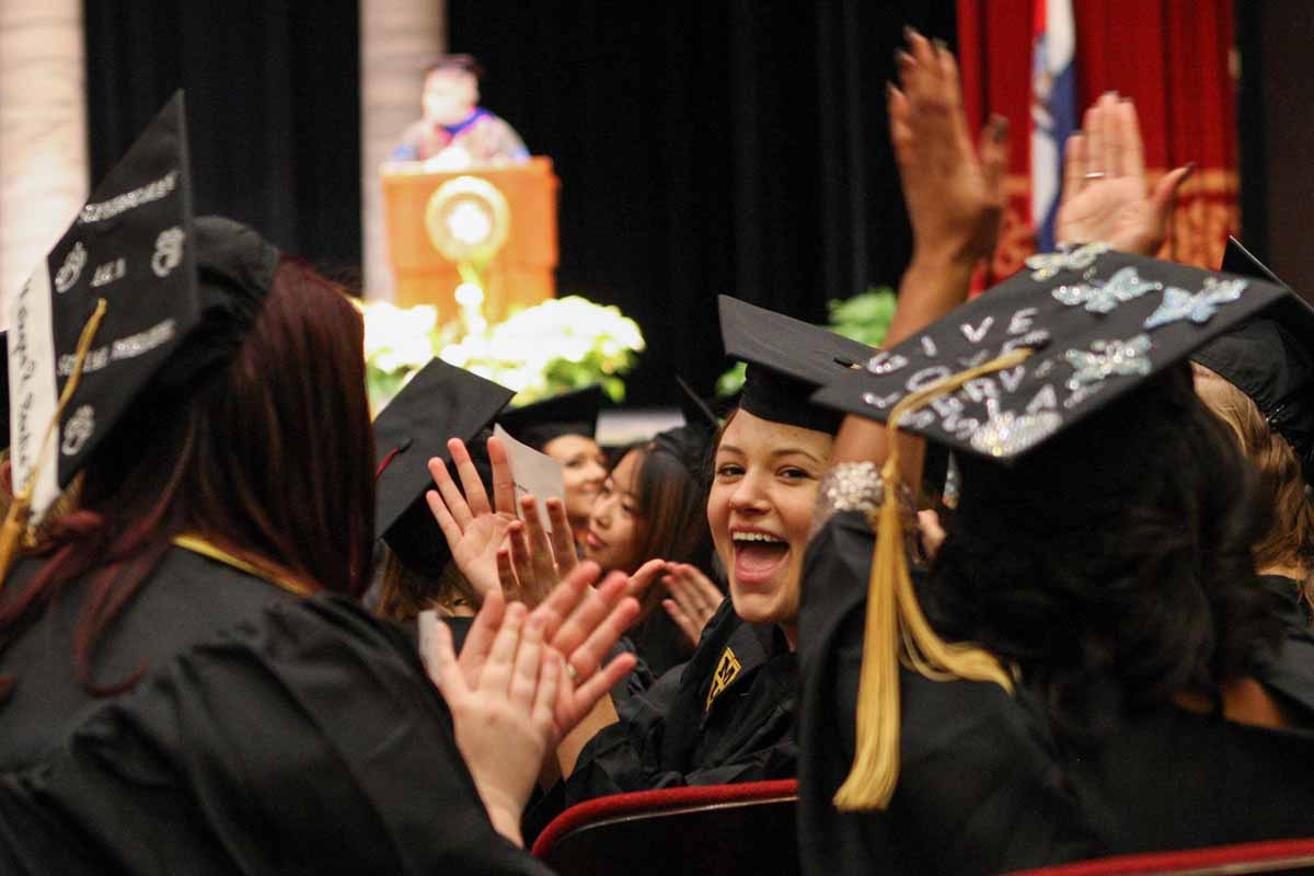 Taylor Starr, a graduate of the School of Social Work, claps for all of the family members as they stand and receive recognition at the beginning of the ceremony in Jesse Auditorium Friday afternoon. Dr. Rob Weagley, the keynote speaker, recognized all parents, relatives and boyfriends/girlfriends that attended the ceremony at the beginning of his speech.