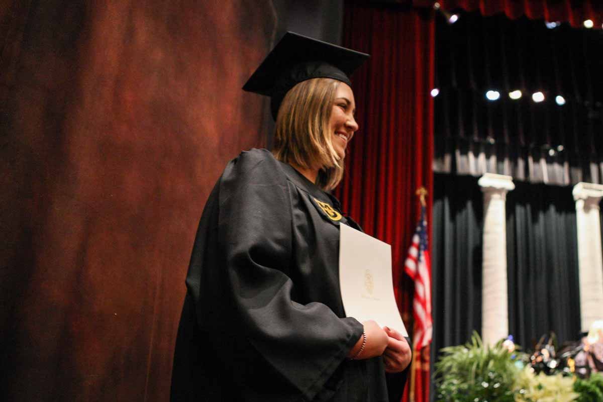 Devon Moltzan poses for a professional portrait with her diploma cover after walking off the stage in Jesse Auditorium Friday afternoon. Moltzan received a bachelors of science-human environmental sciences degree in family and consumer science education.