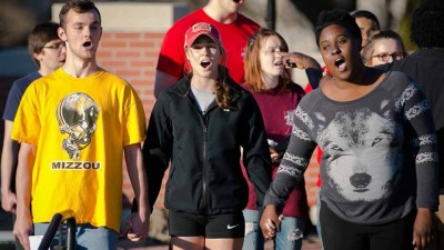 Students holding hands and singing.