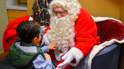 Child touching Santa's beard.