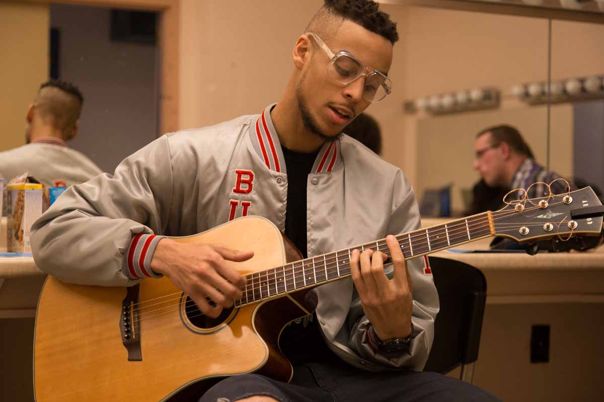 Mizzou Idol contestant Gibraun Mitchell rehearses on the guitar to relieve some nerves before the show begins. Photo by Jake Hamilton.