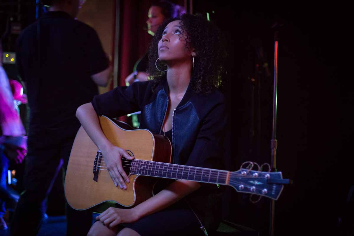 Mizzou Idol contestant Jhaere Mitchell sits backstage with her guitar waiting to perform her first song of the night during the semifinal round. Photo by Jake Hamilton.