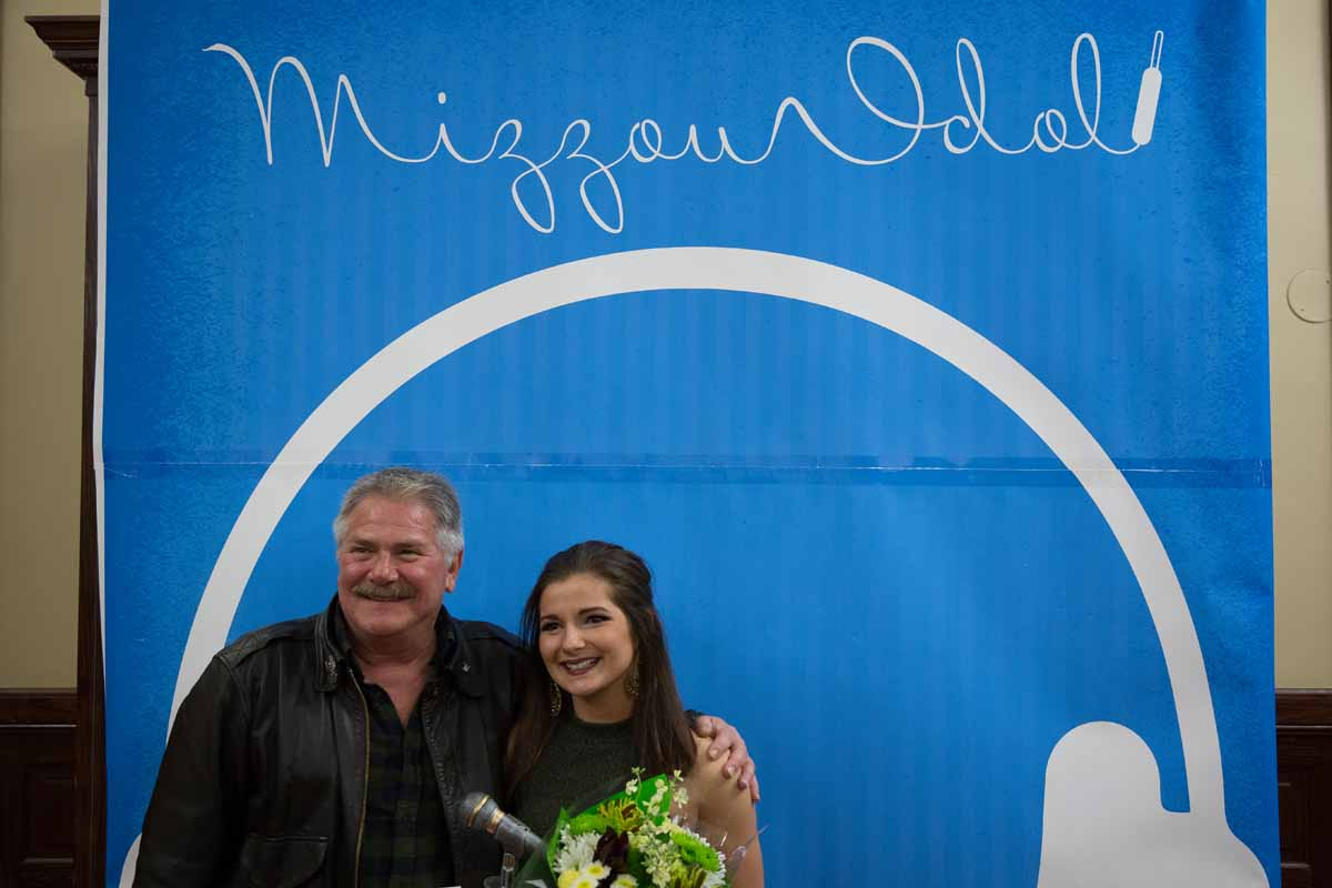 Mizzou Idol winner Breanna Lehane poses with her father in front of the Mizzou Idol 2016 banner after the show. Photo by Jake Hamilton.