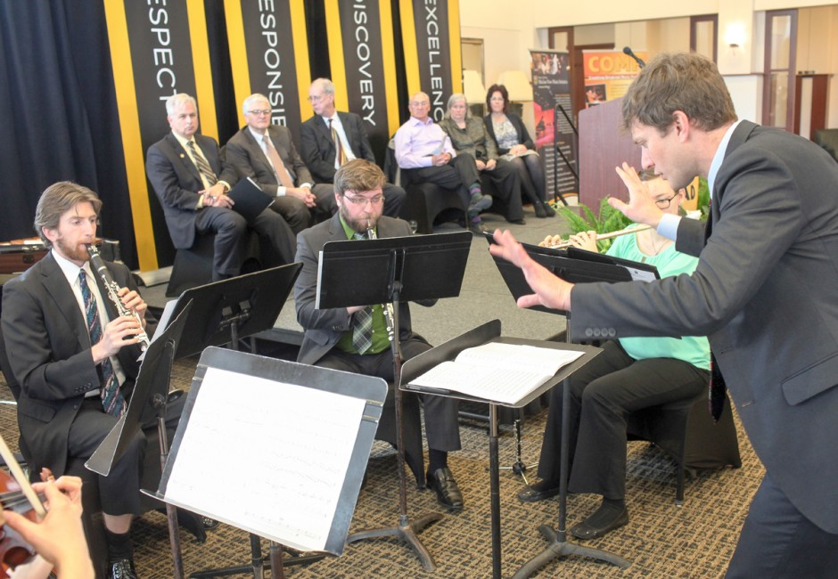 Musicians playing in front of administrators.