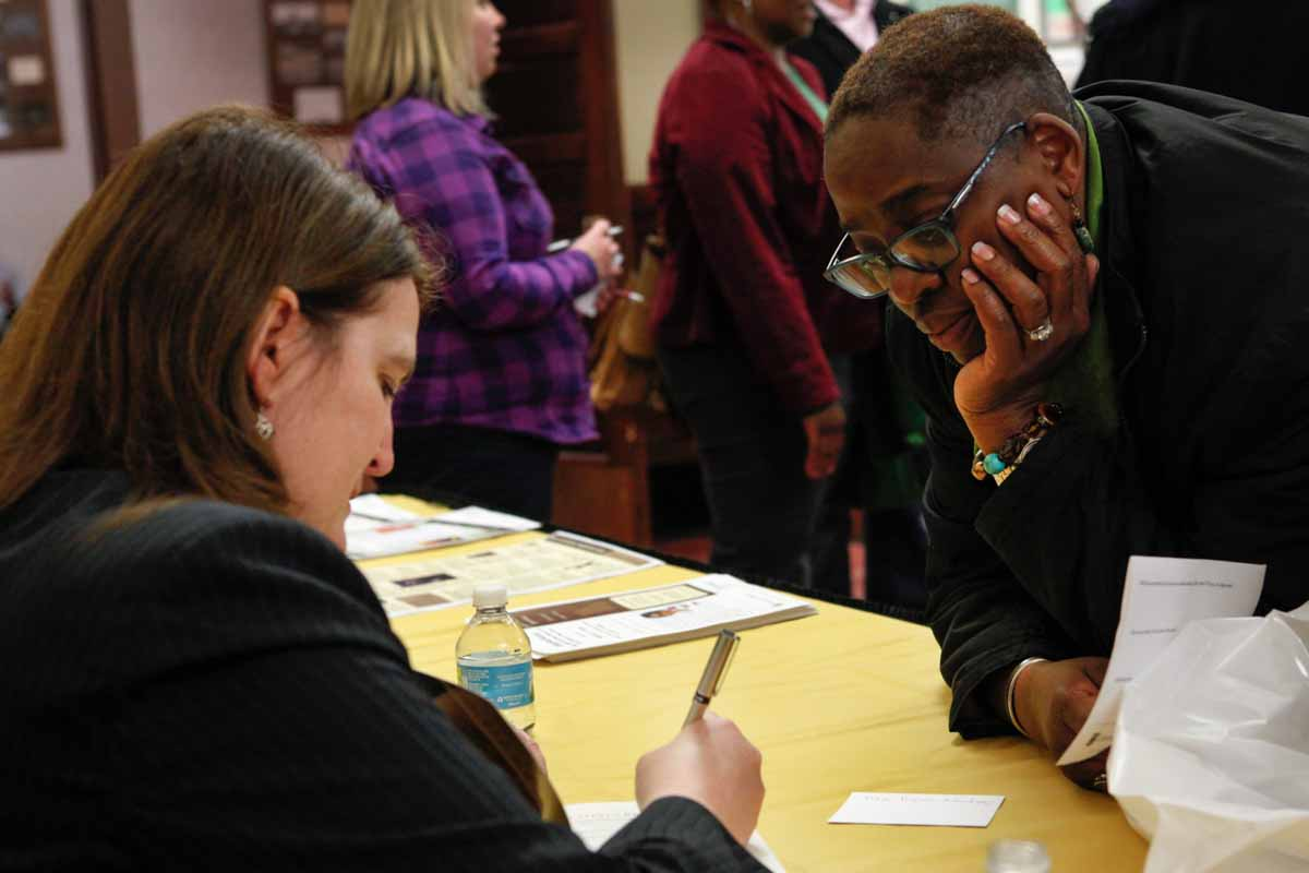 """Traci Wilson-Kleekamp watches intently as her friend, Professor Diane Mutti Burke, signs a copy of """"Contesting Slavery: Enslaved Missourians' Enduring Struggle for Self Determination"""" for her Wednesday evening, Feb. 3, 2016 in the foyer of Jesse Hall. Photo by Tanzi Propst."""