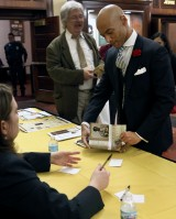 "Interim Vice Chancellor for Inclusion, Diversity and Equity Chuck Henson opens the cover of his newly purchased copy of ""Contesting Slavery: Enslaved MissouriansÕ Enduring Struggle for Self Determination"" so Professor Diane Mutti Burke may sign it Wednesday evening, Feb. 3, 2016 in the foyer of Jesse Hall."