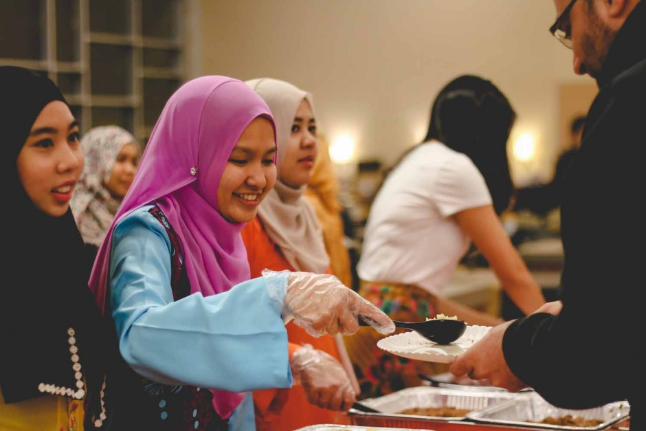 Nisa Ismail, member of the Malaysian Student Association, serves food to an attendee of the International Welcome Party.